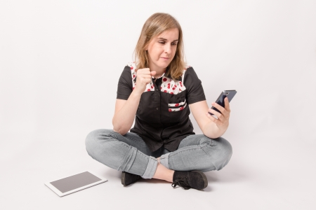 Woman using mobile phone and a tablet on a white background Stock Photo - 21819568