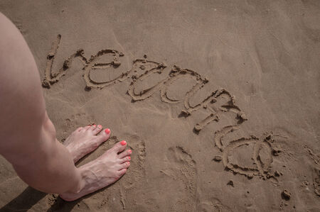Word verano written on sand in the beach of Gandia, Spain photo