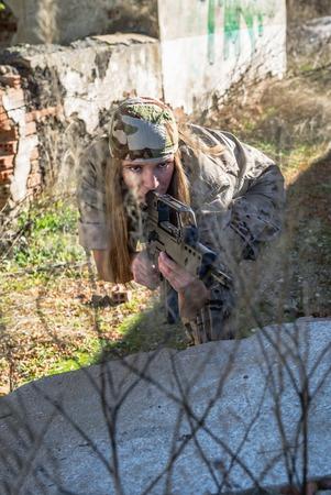 Military woman pointing her gun photo