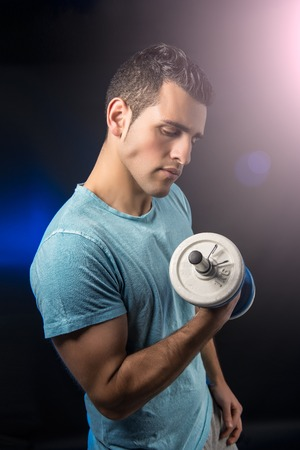 Muscular young man with dumbbells on black background photo