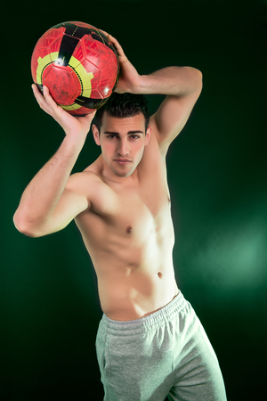 Muscular young man with balloon on green background photo