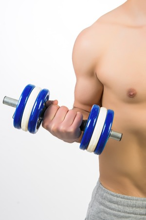 Muscular young man with dumbbells on white background photo