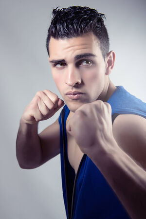 Muscular young man in boxing stance on gray background