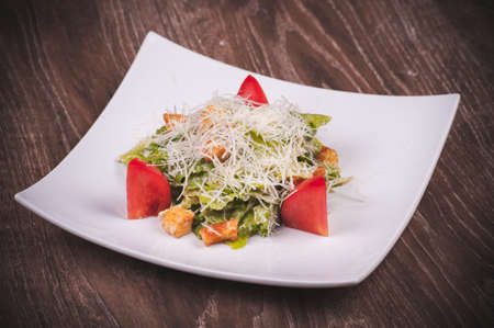 crouton: vegetarian cesar salad with tomato, croutons and cheese on white plate Stock Photo