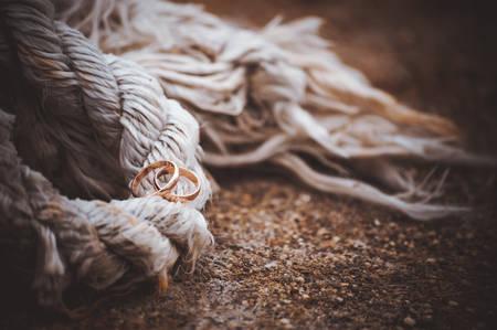 bonding rope: two wedding rings laying on old rope