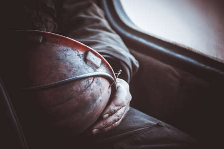 durty hands of miner worker hold helmet no face Stock Photo