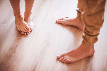barefoot teens: barefoot couple standing on wooden floor no face Stock Photo