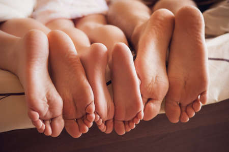young woman face: close up of a family showing off their feet under the covers. no face Stock Photo