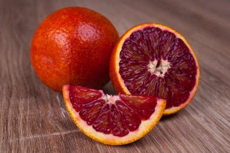 붉은 피 시칠리아 오렌지 전체, 절반 및 나무 배경에 wegde