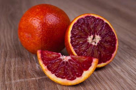 red blood sicilian orange whole, half and wegde on wooden background Reklamní fotografie