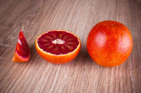 red blood sicilian orange whole, half and wegde on wooden background Stock Photo