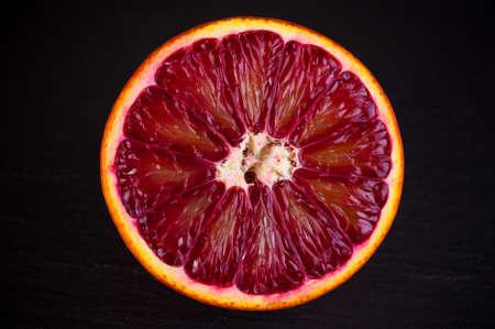 half  cut: slice of red blood sicilian orange on black stone background