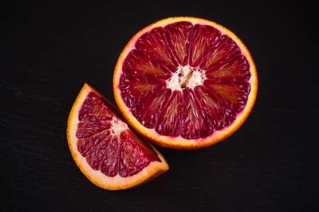 red blood sicilian orange wedge and half on black stone background