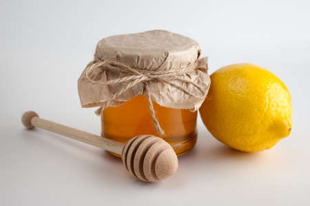 Honey in jar and lemon on a  white background photo