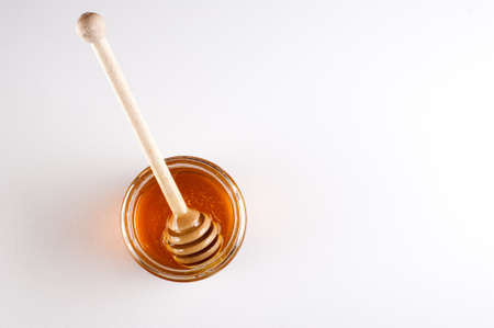 honey jar: Glass can full  of honey and wooden stick in it.