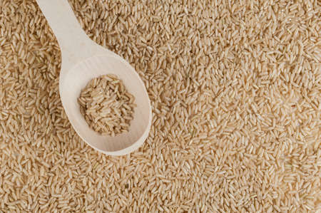 unpolished: Unpolished brown rice texture with wooden spoon . top view