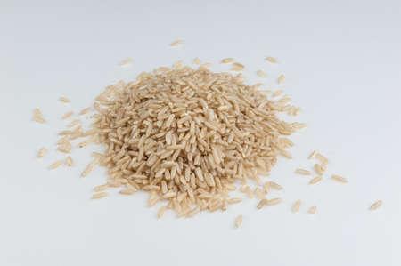 heap of unpolished organic rice isolated on white