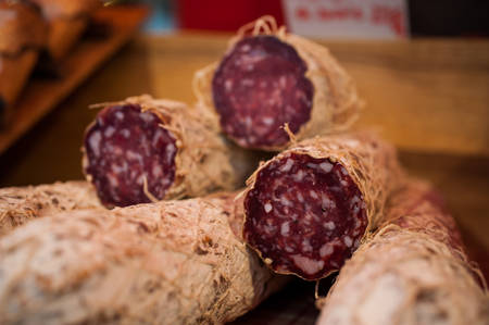 red meat: pile of salami cut in a half sold on market