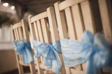 wedding chairs: Wedding chairs in raw decorated in blue color Stock Photo