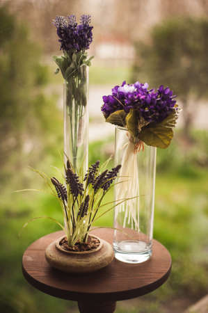 small table: Vases with purple flowers on the small table