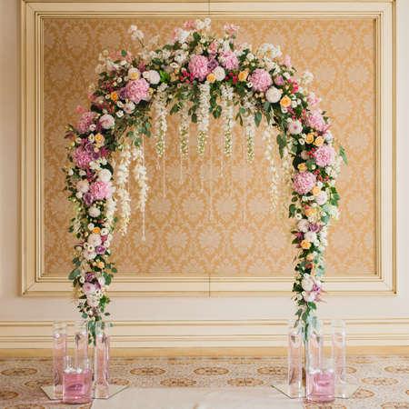 실내에 혼합 된 화려한 꽃으로 장식 된 아치 밑의 통로