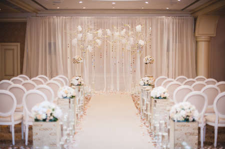 Beautiful wedding ceremony design decoration elements with arch, floral design, flowers, chairs indoor Reklamní fotografie
