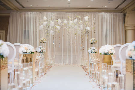 Beautiful wedding ceremony design decoration elements with arch, floral design, flowers, chairs indoor Фото со стока