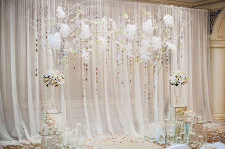 wedding table decor: Beautiful wedding ceremony design decoration elements with arch, floral design, flowers, chairs indoor Stock Photo