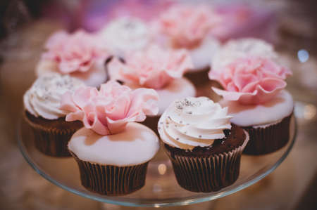 high tea: Colorful sweet cupcakes on plate . pink and white