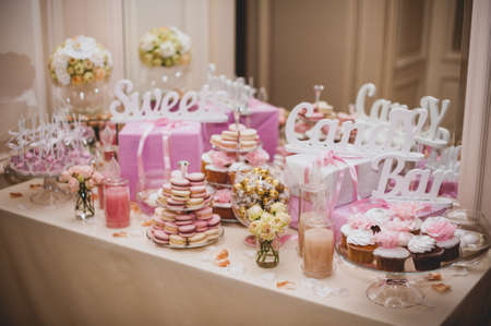 wedding table decor: party reception, decorated desert table pink color Stock Photo
