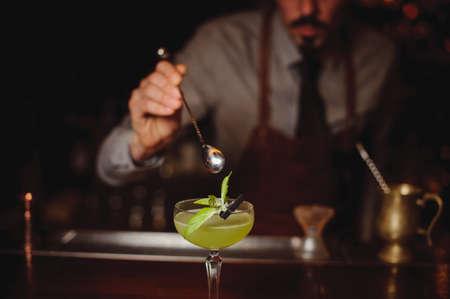 cocteles de frutas: Primer plano de barman hace el coctel verde en la barra de Foto de archivo