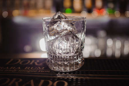 bar top: Empty glass with ice rock on bar top