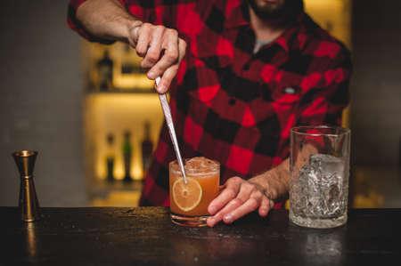 バーテンダー作り、オレンジ色のカクテルのクローズ アップを飾る