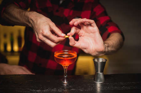 squeezing: male bartender is squeezing orange peel into a cocktail glass