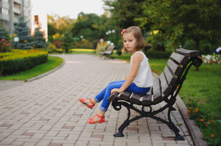 lost: sad little girl sitting on the bench in the park at the day time