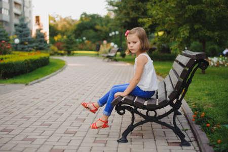 trauriges kleines Mädchen auf der Bank an der Tageszeit sitzen im Park