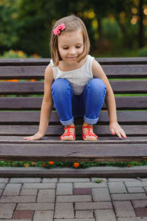 quick hedge: Little cute girl sits with feet on bench Stock Photo