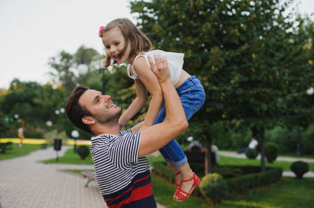 throws: Happy family Dad throws child daughter up on a walk in the autumn leaf fall in park