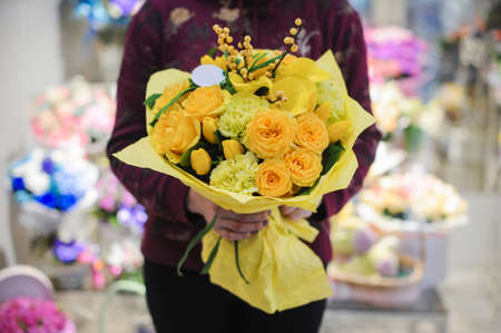 wedding customs: Beautiful yellow bouquet of roses and other flowers in hands Stock Photo