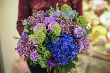 gree: bouquey of gree, purple and blue flowers  in hands