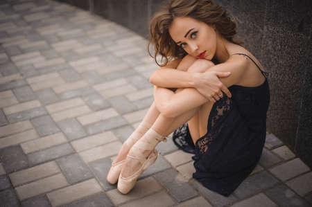 junges Mädchen Balletttänzer im schwarzen Kleid und Spitzenschuhe auf dem Boden sitzen