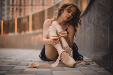 Ballet dancer sitting on the ground and putting on her pointe shoes. Main focus on the legs