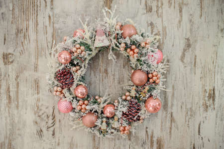 christmas wreath with pink decor and bubbles on wooden background