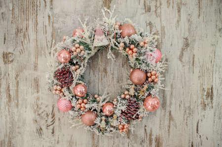 Corona de Navidad con la decoración de color rosa y burbujas en el fondo de madera Foto de archivo - 49117428