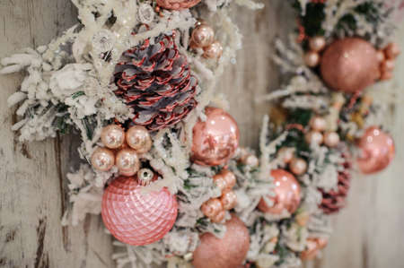 christmas wreath with pink decor and bubbles on wooden background close up