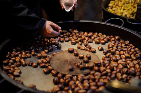 men roasting chestnuts  ready to eat . no face