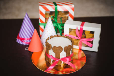 dog cake and cookie in boxes with ribbons and birthday hats