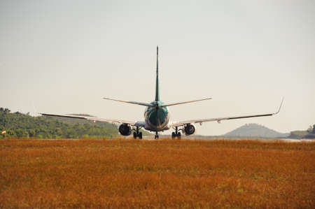 take off: Passenger jet plane on the runway in the airport. Back view. Travel background Stock Photo