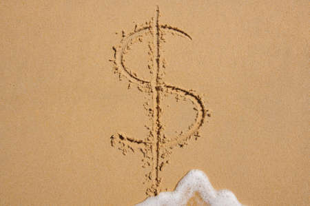 sand dollar: Dollar sign in beach sand being washed away by wave