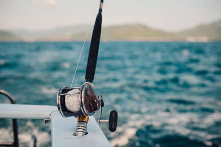 marlin: Boat fishing rods over a beautiful cloudy seascape horizontal